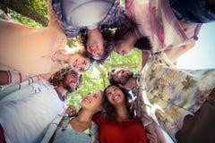 Amis heureux formant un petit groupe en parc Photos libres de droits