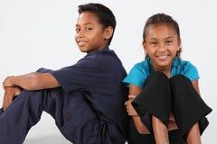 Amis heureux garçon et fille d'école s'asseyant ensemble Images stock