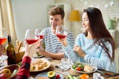 Amis heureux grillant au dîner de thanksgiving Photo stock