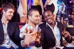 Amis heureux grillant avec de l'alcool Image libre de droits