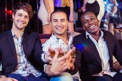 Amis heureux grillant avec de l'alcool Images libres de droits