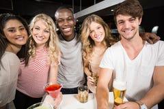Amis heureux grillant avec de la bière et des cocktails Images libres de droits