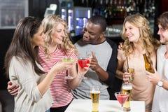 Amis heureux grillant avec de la bière et des cocktails Image libre de droits