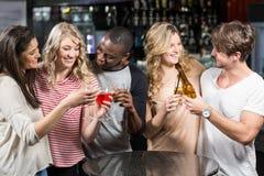 Amis heureux grillant avec de la bière et des cocktails Photos libres de droits