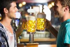 Amis heureux grillant avec des cruches de bière Photographie stock
