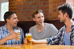 Amis heureux grillant avec des pintes de bière Photo stock