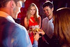 Amis heureux grillant avec le champagne Photographie stock