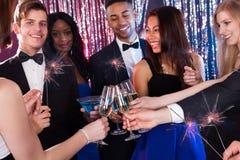 Amis heureux grillant des boissons à la boîte de nuit Photographie stock libre de droits