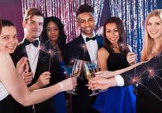 Amis heureux grillant des boissons à la boîte de nuit Image libre de droits