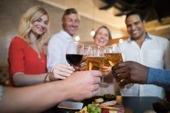 Amis heureux grillant des boissons Photo libre de droits