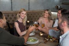 Amis heureux grillant des boissons tout en dinant Photographie stock