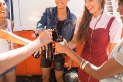 Amis heureux grillant des bouteilles à bière Photo stock