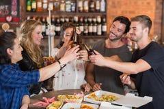 Amis heureux grillant des bouteilles à bière au-dessus des pizzas sur la table Image stock