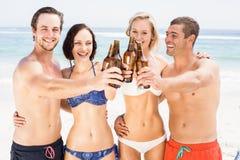 Amis heureux grillant des bouteilles à bière sur la plage Image libre de droits