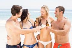Amis heureux grillant des bouteilles à bière sur la plage Photographie stock libre de droits