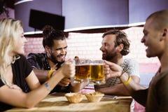 Amis heureux grillant des tasses de bière à la boîte de nuit Photo libre de droits