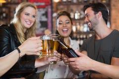 Amis heureux grillant des tasses et des bouteilles de bière Photographie stock libre de droits