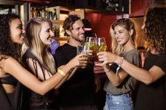 Amis heureux grillant des verres de bière Images stock