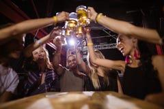 Amis heureux grillant des verres de bière tout en se reposant à la table Photos libres de droits