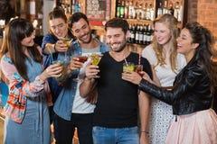 Amis heureux grillant des verres de boissons Images stock