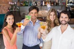 Amis heureux grillant des verres de cocktail Image libre de droits