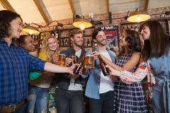 Amis heureux grillant des verres et des bouteilles de bière dans le bar Photos libres de droits
