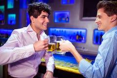 Amis heureux grillant la bière Photographie stock
