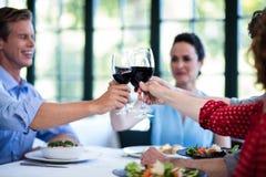 Amis heureux grillant le verre de vin tout en prenant le déjeuner Photos libres de droits