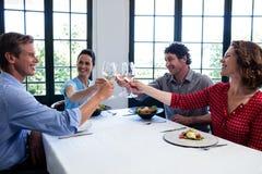 Amis heureux grillant le verre de vin tout en prenant le déjeuner Image libre de droits