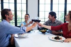 Amis heureux grillant le verre de vin tout en prenant le déjeuner Photo libre de droits