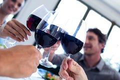 Amis heureux grillant le verre de vin tout en prenant le déjeuner Photographie stock