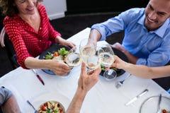 Amis heureux grillant le verre de vin tout en prenant le déjeuner Photo stock