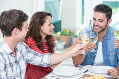 Amis heureux grillant le vin blanc Photographie stock