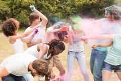 Amis heureux jetant la peinture de poudre Photo stock