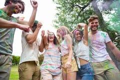 Amis heureux jetant la peinture de poudre Image libre de droits