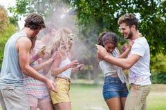 Amis heureux jetant la peinture de poudre Images stock