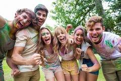 Amis heureux jetant la peinture de poudre Photographie stock libre de droits