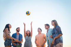 Amis heureux jetant le volleyball Image stock