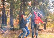 Amis heureux jouant avec la boule en parc Photo stock