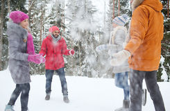 Amis heureux jouant avec la neige dans la forêt d'hiver Photographie stock libre de droits