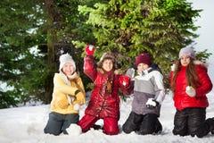 Amis heureux jouant des boules de neige à la forêt d'hiver Photos libres de droits