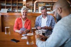 Amis heureux jouant des cartes tout en ayant le verre de bière Image libre de droits