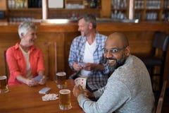 Amis heureux jouant des cartes tout en ayant le verre de bière Photo stock