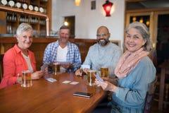 Amis heureux jouant des cartes tout en ayant le verre de bière Image stock