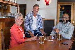 Amis heureux jouant des cartes tout en ayant le verre de bière Photo libre de droits