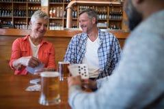 Amis heureux jouant des cartes tout en ayant le verre de bière Photos libres de droits