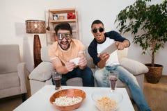 Amis heureux jouant des jeux d'ordinateur Photo stock