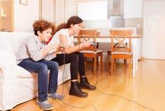 Amis heureux jouant des jeux vidéo à la maison Photographie stock libre de droits