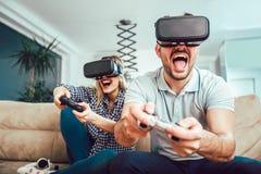 Amis heureux jouant des jeux vidéo avec des verres de réalité virtuelle Images libres de droits