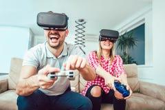 Amis heureux jouant des jeux vidéo avec des verres de réalité virtuelle Photos stock